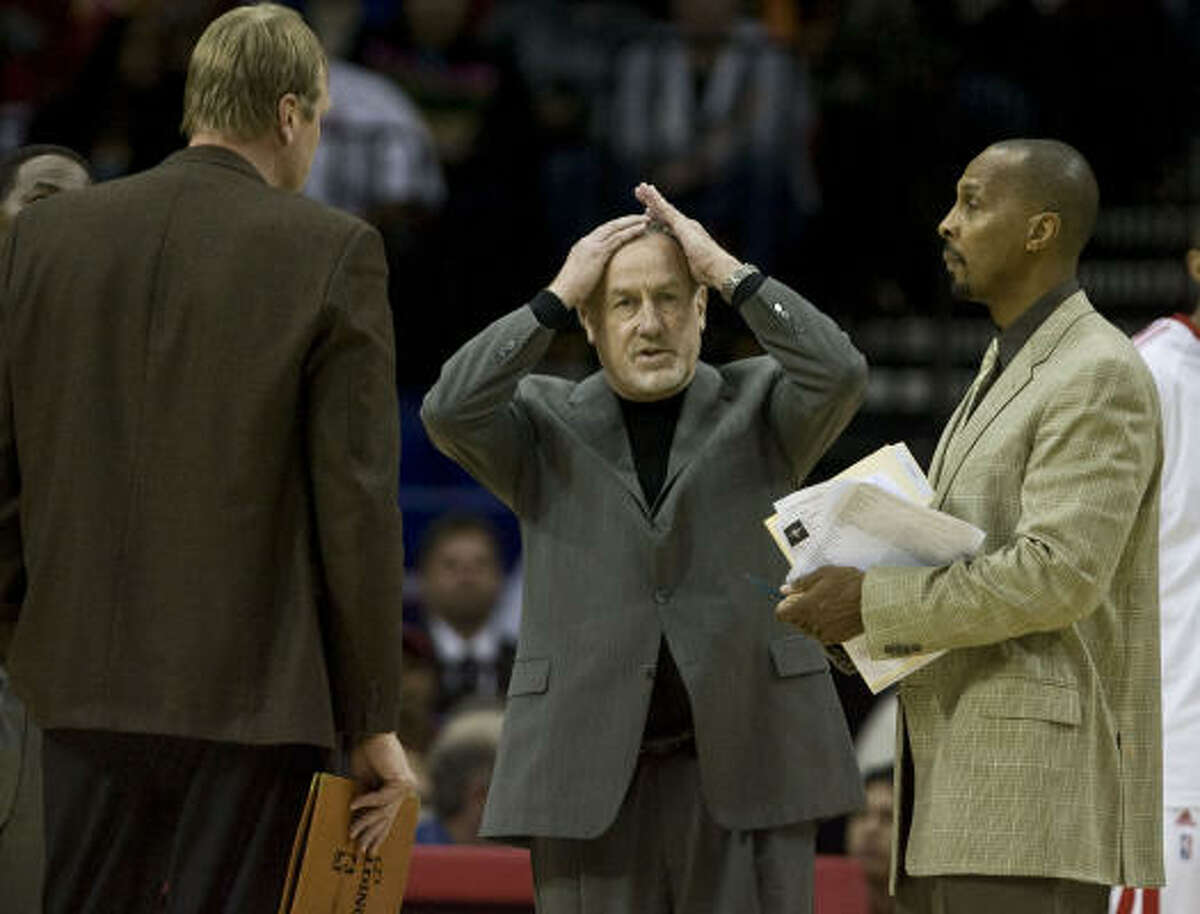 Rockets head coach Rick Adelman (center) rubs his head during a timeout as assistant coaches Jack Sikma (left) and Elston Turner (right) look on during the fourth quarter.