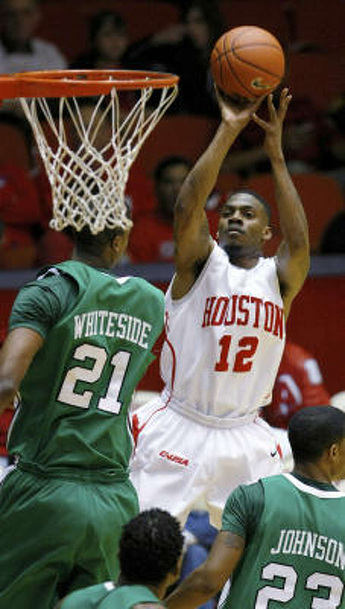 UH guard Aubrey Coleman pulls up for a jumper as Marshall forward Hassan Whiteside and the defense collapse on him in the second half.