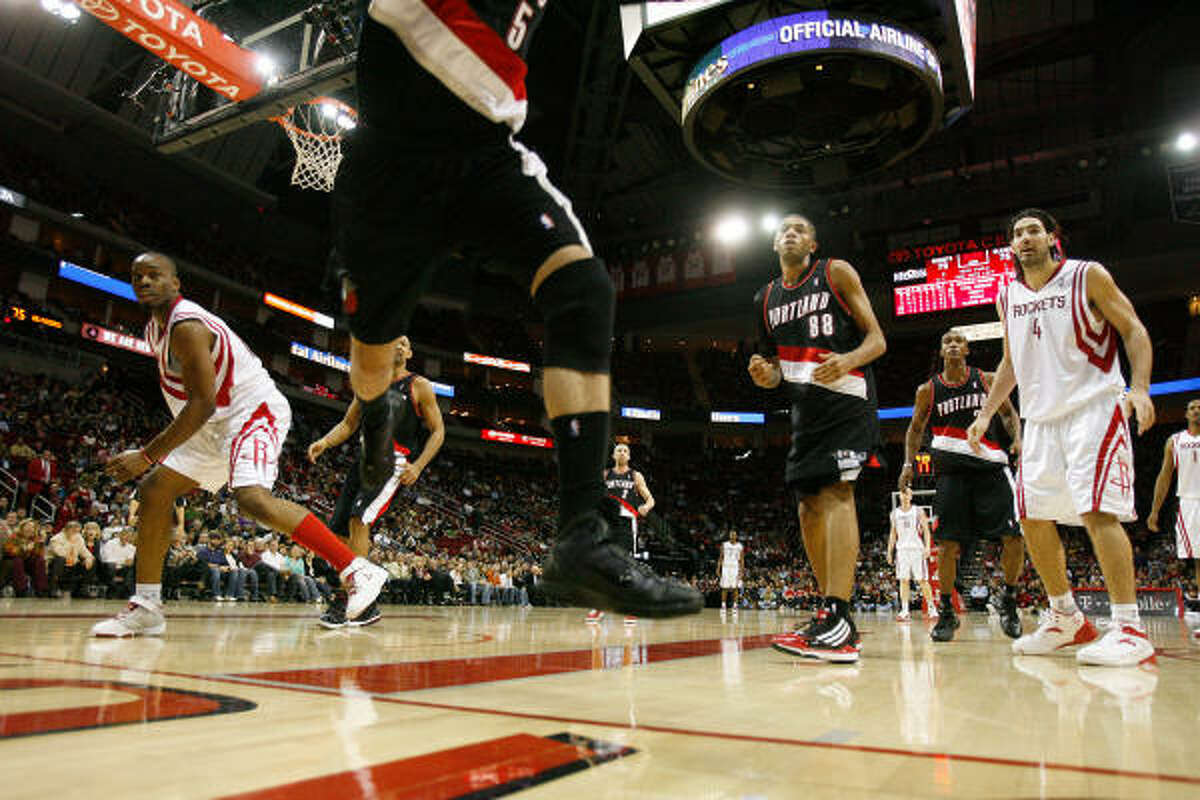 Rockets forward Carl Landry, left, watches Trail Blazers guard Rudy Fernandez go crashing into the stands in the fourth quarter.