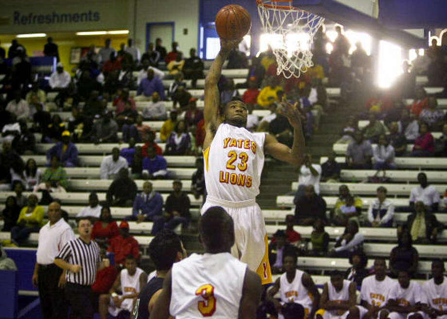 Brandon Peters goes up for a dunk as Yates High School basketball fans watch their team play against Austin at Barnett Fieldhouse in Houston.  Yates went on to win the game 142-52. The success of the Yates basketball team has had an impact on the community over the season. Photo: Michael Paulsen, Chronicle