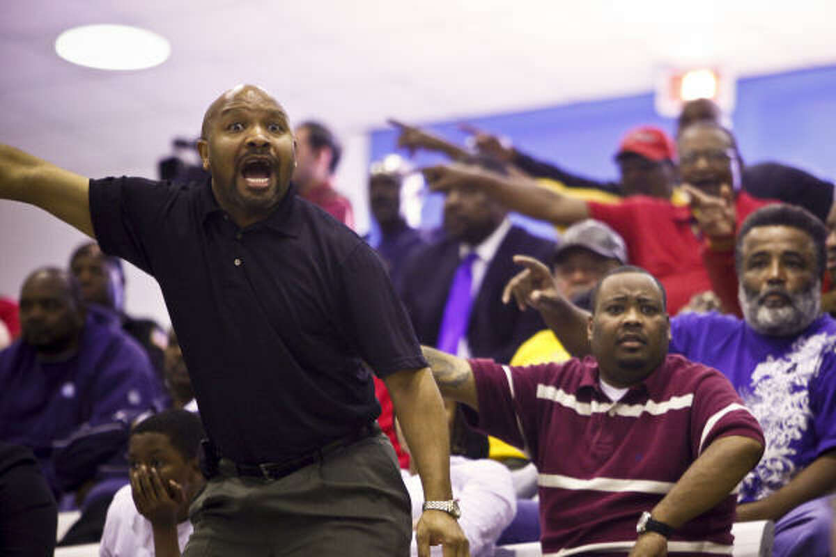 Phil Davis and other Yates High School basketball fans react while watching their team play against Austin at Barnett Fieldhouse.