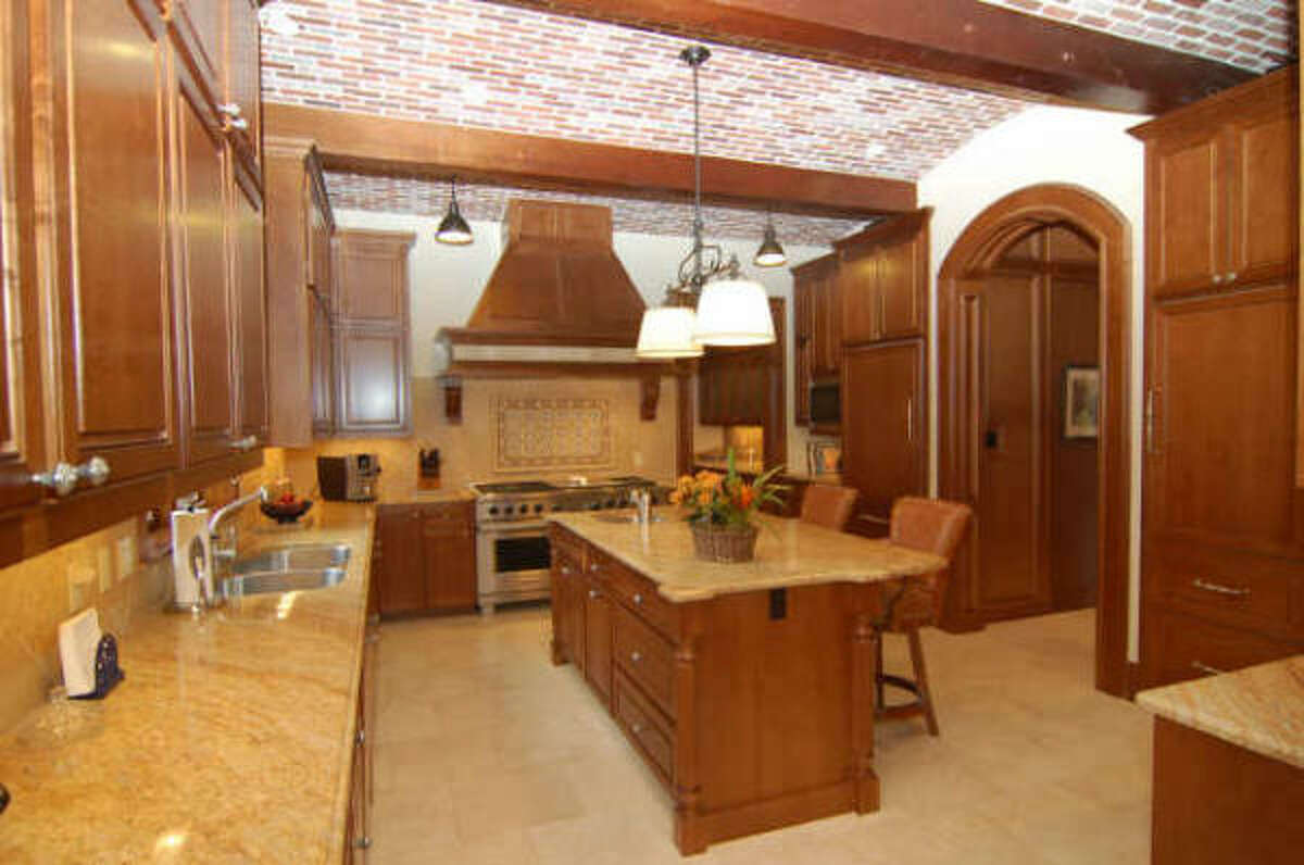 Kitchen offers a barrell vaulted ceiling with solid wood beams, custom stained cabinetry, Wolf range, 2 dishwashers, veggie sink, warmer drawer, 4 freezer drawers, 2 refrigerator drawers, Butler's pantry, and self close draw slides.