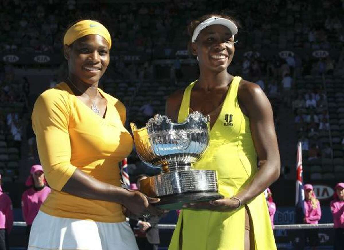 Serena, left, and Venus Williams hold the trophy after beating Cara Black and Liezel Huber 6-4, 6-3 to win the doubles title.