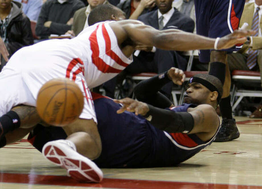 Atlanta's Josh Smith is still able to get off a pass from the ground under pressure from Carl Landry. Photo: Melissa Phillip, Chronicle