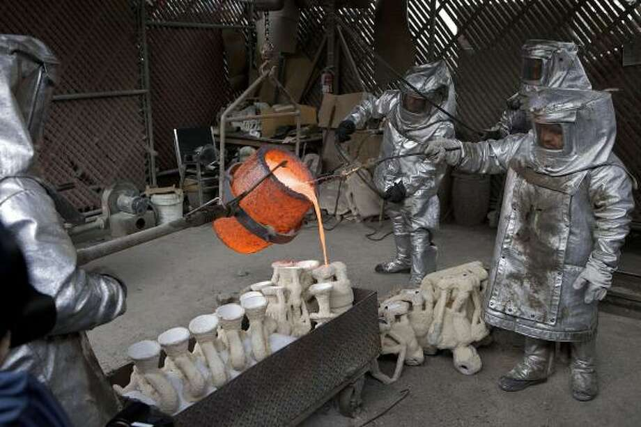 "Workmen pour molten bronze metal into cast molds for the Screen Actors Guild Award's ""The Actor"" statuettes. Photo: Damian Dovarganes, AP"