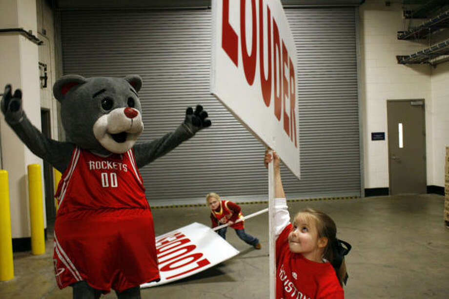 Clutch, aka, Robert Boudwin, the Houston Rockets mascot, gets that nights Clutch Jr. helpers, Carol Ann Caswell, 8, and Rachael Marglous, 9, tips before a game against the Miami Heat. Photo: Johnny Hanson, Chronicle