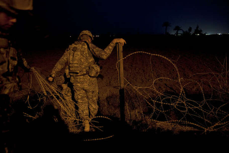 Soldiers from the 72nd Infantry Brigade Combat Team climb through razor wire to begin a pre-dawn foot patrol mission in Baghdad, Iraq. The 72nd Infantry Brigade Combat Team's Quick Response Force in Camp Cropper surveyed the perimeter of exterior wall for any tampering. Photo: Mayra Beltran, Chronicle