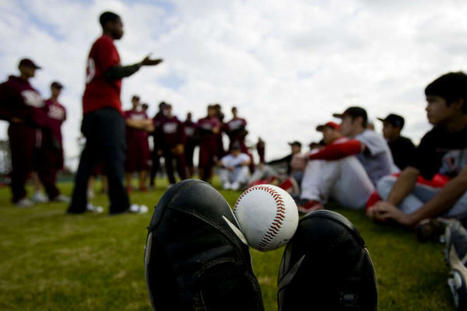 With a baseball propped between his toes, Ken' Andra James, 16, of Houston listens to Astros pitcher Wesley Wright, left, give tips to high school and Texas Southern University baseball players at MacGregor Park. Photo: Johnny Hanson, Chronicle