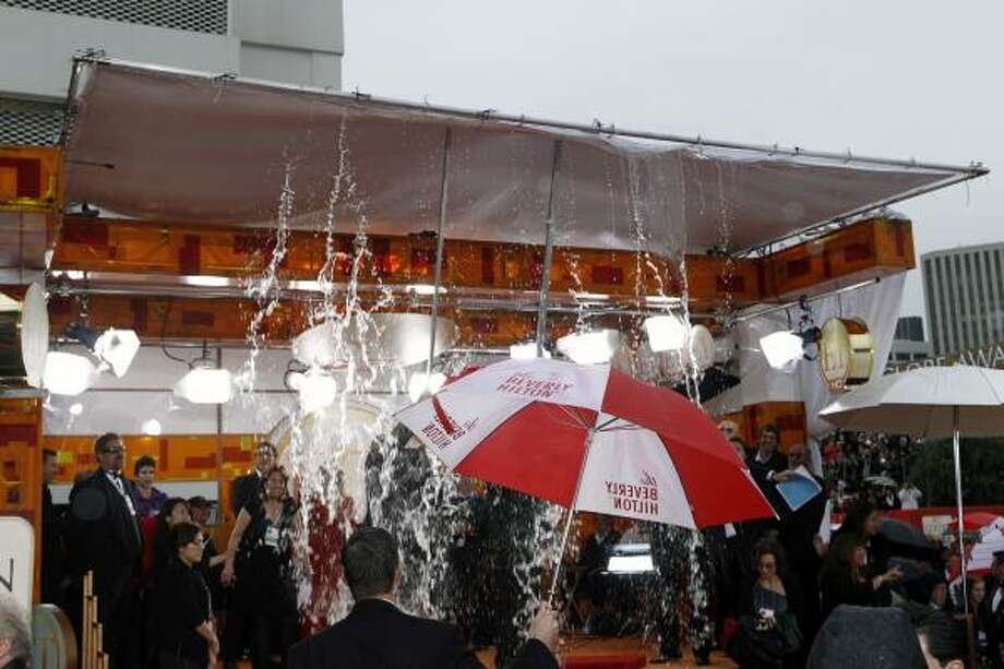 Rainwater is knocked from a tent roof before the 67th Annual Golden Globe Awards. Photo: Matt Sayles, AP