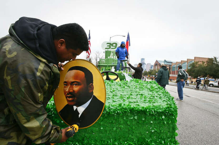 Vidal Martinez removes a Martin Luther King Jr. sign from a float after the parade along Allen Parkway. Photo: Michael Paulsen, Chronicle