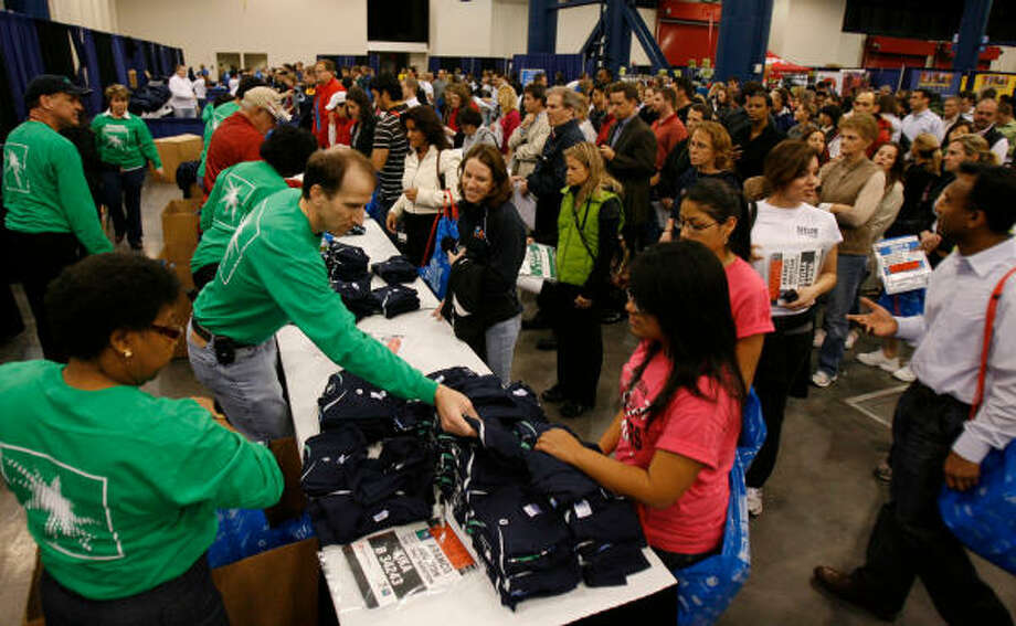 Runners pick up their gear in preparation for Sunday's Chevron Houston Marathon at the George R. Brown Convention Center. Photo: Julio Cortez, Chronicle