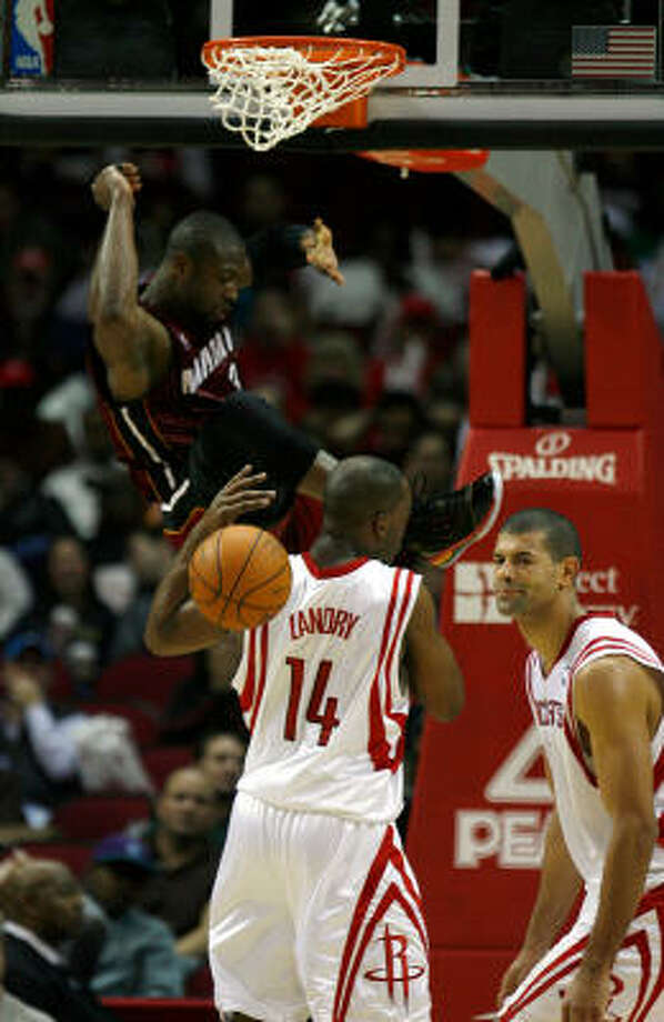 The Rockets had a tough time defending Miami guard Dwayne Wade, top, in Friday night's game at Toyota Center. Wade scored a game-high 37 points and added eight assists to lead the Heat past the Rockets, 115-106. Photo: Johnny Hanson, Chronicle