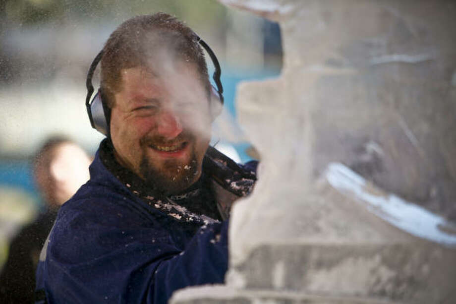 "Dan Rebholz, one of only five certified ""Master Carvers"" in the USA, uses a chainsaw to sculpt a creation out of ice blocks during the Magnificent Seven All Out Ice Sculpting Competition at Discovery Green. Photo: Michael Paulsen, Chronicle"