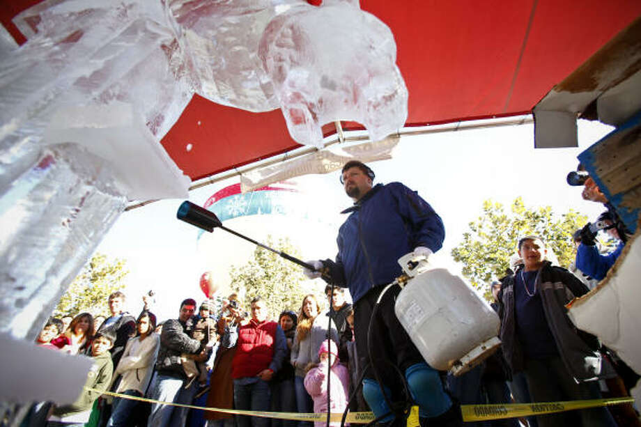 "Dan Rebholz, one of only five certified ""Master Carvers"" in the USA, uses a propane torch to melt ice imperfections in his sculpture during the Magnificent Seven All Out Ice Sculpting Competition at Discovery Green. Photo: Michael Paulsen, Chronicle"