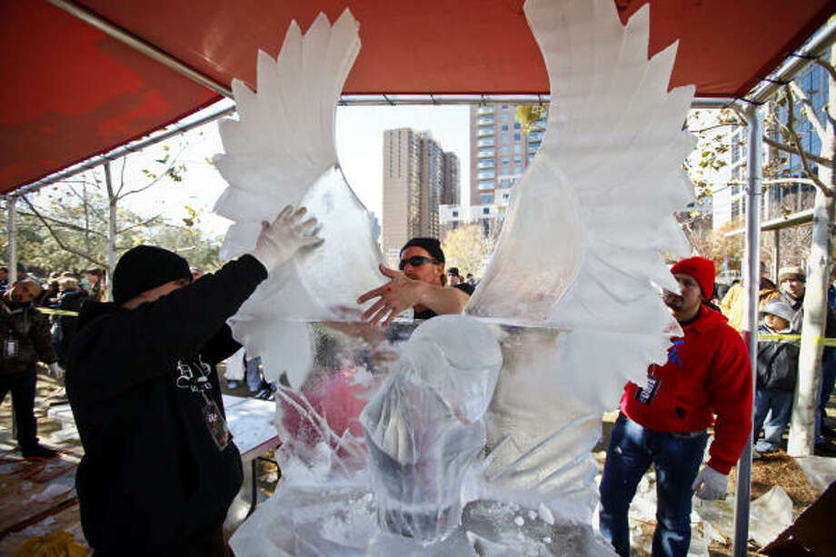 Buddy Rasmussen of the Team Texas Chainsaw Massacre mounts ice wings on his sculpture during the Magnificent Seven All Out Ice Sculpting Competition at Discovery Green. Seven of the best ice sculptors in the world visited Discovery Green to battle for bragging rights and a cash grand prize. Photo: Michael Paulsen, Chronicle