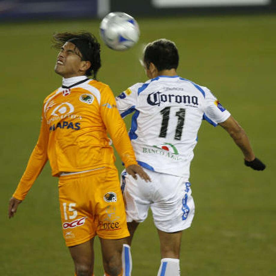 Puebla 1, Jaguares 0Jaguares midfielder Gerardo Flores, left, and Puebla defender Gilberto Mora go upfor the ball in the first half. Photo: Julio Cortez, Chronicle
