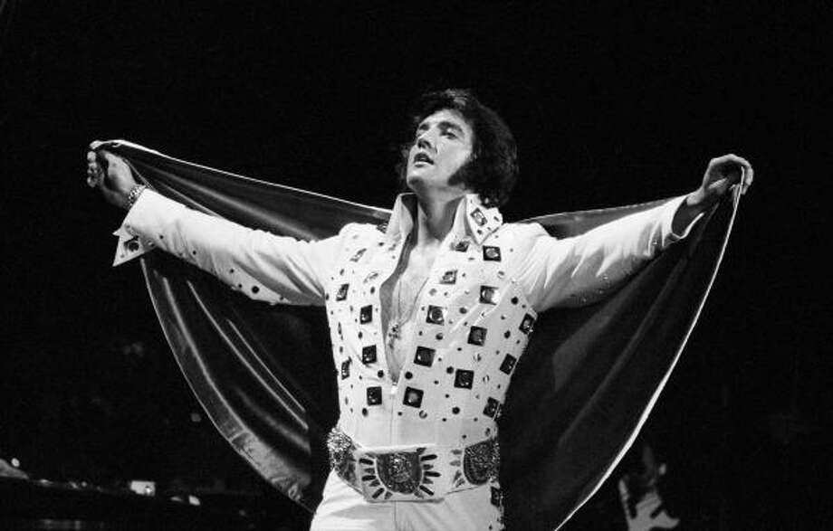 "Paganism:His bejeweled jumpsuits were covered with ""occult"" symbols: horseshoes, owls, crosses, zodiacs.  Here, at Madison  Square Garden, he's rockin' an ankh necklace and a belt so tacky I can't tell what's on it. Photo: George Kalinsky, AP"