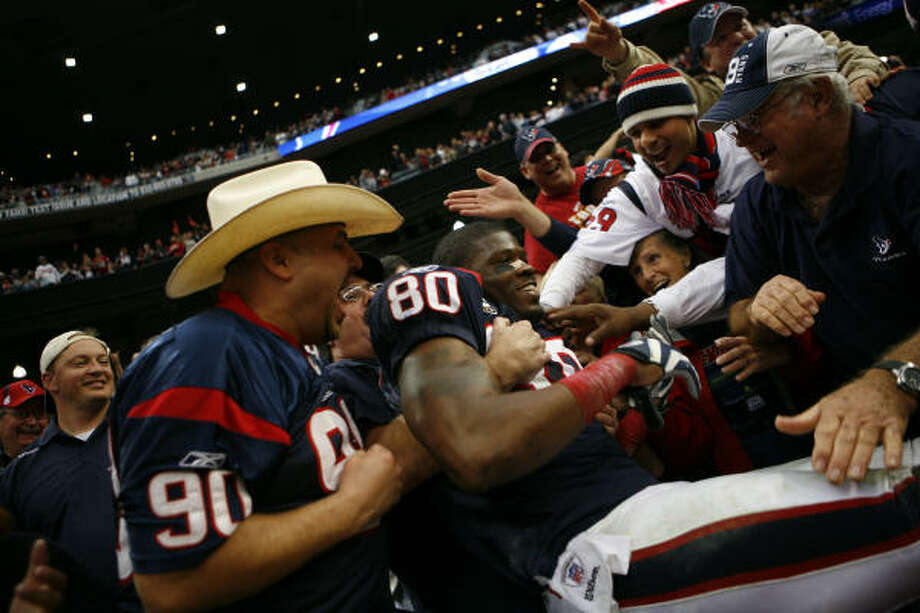 Wide receiver Andre Johnson jumps into the crowd to celebrate with fans following the Texans' 34-27 victory over the New England Patriots. Photo: Nick De La Torre, Chronicle