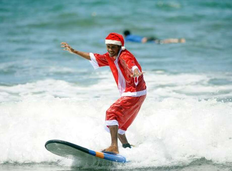 A surfer dressed in a Santa costume surfs at Kuta beach on the Indoensian resort island of Bali on Christmas Eve. Photo: SONNY TUMBELAKA, AFP/Getty Images
