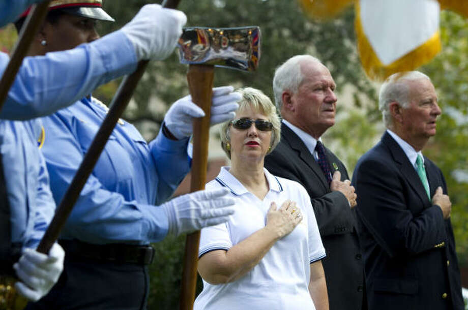 Mayor Annise Parker, center, stands for the National Anthem with Lawrence Catuzzi and former Secretary of State James A. Baker III during the dedication ceremony of Lauren's Garden at Market Square Park in Houston. The garden is a gift to the City of Houston from the Lauren Catuzzi Grandcolas Foundation in memory to all those who lost their lives in the 9/11 attacks. Grandcolas was the only Houstonian aboard United Airlines Flight 93. Photo: Brett Coomer, Chronicle