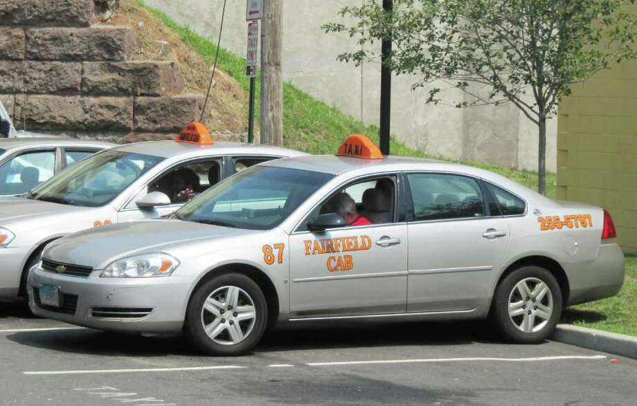 Pictured are two vehicles that belong to the Fairfield Cab Company, which has run into problems recently with vehicles being removed from the road and two drivers being arrested this month, one for buying for alcohol for minors, and the other for sexually assaulting a teen passenger. In addition, Fairfield Cab, which used to be the town's only cab company, is now facing competition from Red Dot Taxi Service. Red Dot's cabs are converted Lincoln Town Cars. Photo: Contributed Photo / Fairfield Citizen contributed