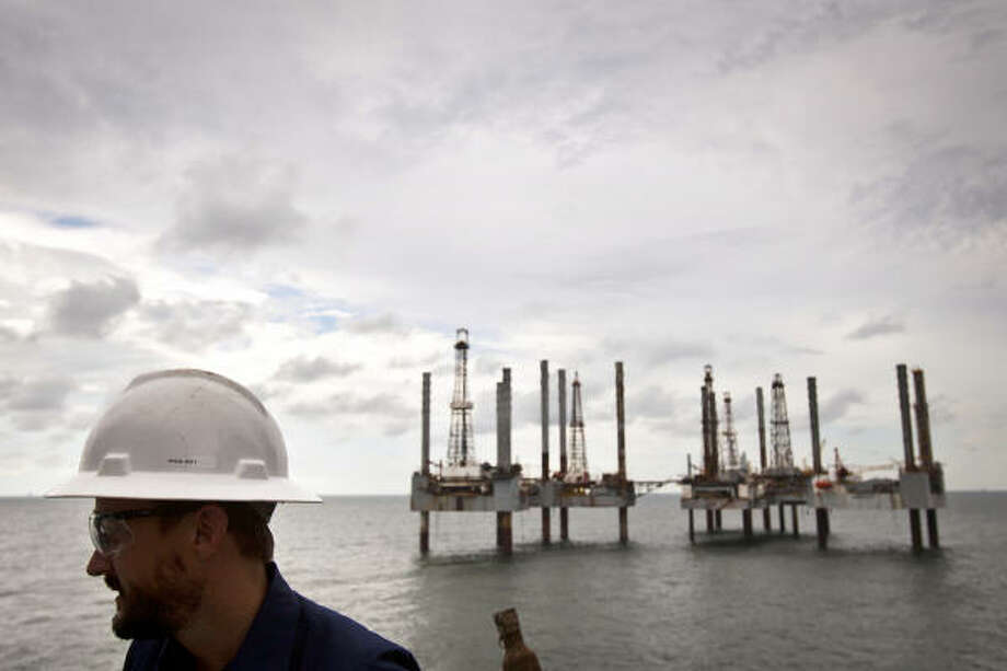 A group of idle rigs is seen behind James Noe, Senior Vice President, General Counsel and Chief Compliance Officer for Hercules Offshore, while aboard the Hercules 25, a shallow water drilling rig near Port Fourchon, La.. While shallow offshore drilling is not subject to a federal moratorium, Hercules officials say only two permits have been issued since June, idling activity in their fleet. The company has about 250 employees on idle rigs, with each rig costing the company about $25,000 per day to operate while generating no revenue for the company. Photo: Smiley N. Pool, Chronicle