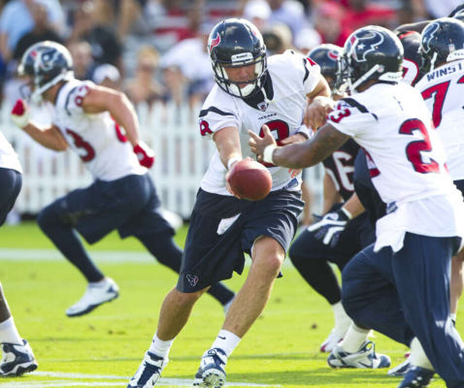 Texans quarterback Matt Schaub (8) hands the ball off to running back Arian Foster (23) during the first day of training camp. Photo: Brett Coomer, Chronicle