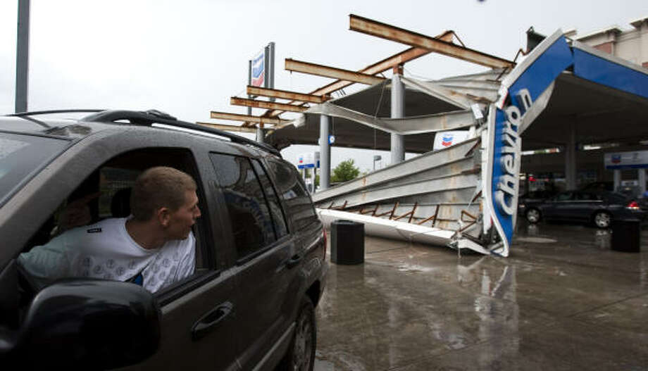 Brett Thompson looks out his driver's side window Wednesday at the downed canopy at a gas station at the intersection of Weslayan and the Southwest Freeway. Isswar Desai, owner of the Chevron station, said there was heavy rain and he was helping a customer when he heard a large crash. He added that it was lucky that there were no customers getting gas where the awning came down. There were no injuries reported. Photo: Brett Coomer, Chronicle