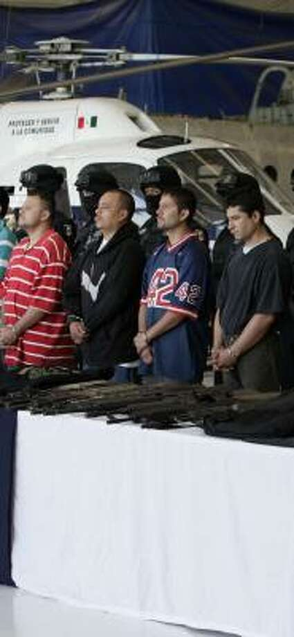 Alleged members of the Mexican drug cartel nown as La Familia Michoacana wait during their presentation at police headquarters in Mexico City. Photo: Gregory Bull, AP