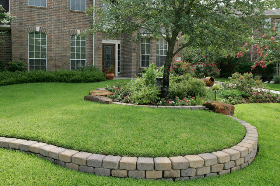 A Curving Retaining Wall Of Tumbled Concrete Blocks Snakes Across The  Terraced St. Augustine Lawn