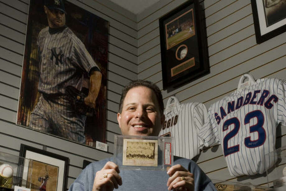 Houstonian Jeffrey Rosenberg holds an 1869 card picturing baseball's first pro team, the Cincinnati Red Stockings, which he won in an eBay auction. Fewer than 10 are known to exist. Photo: Sharon Steinmann, Chronicle