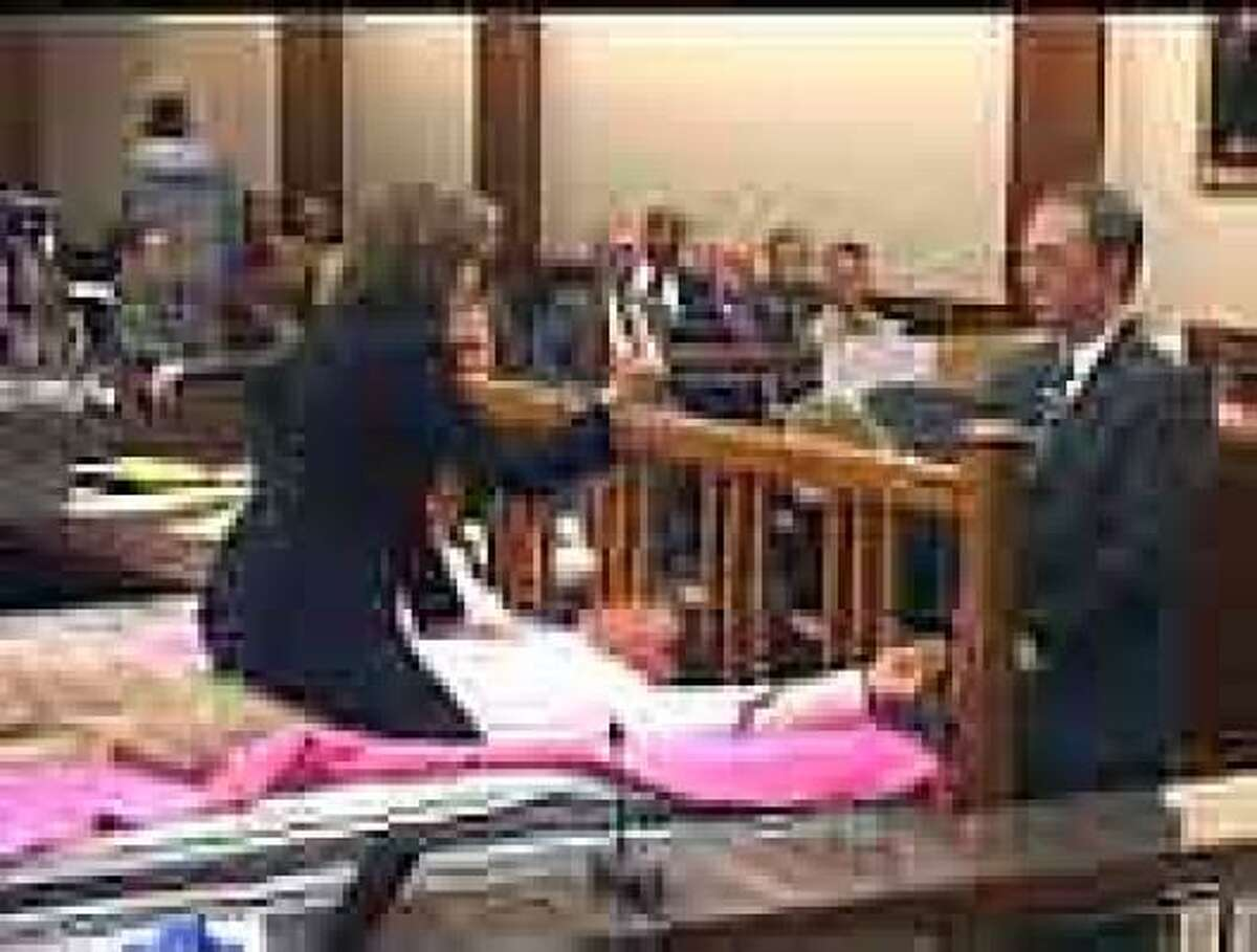 Harris County prosecutors Kelly Siegler and Paul Doyle demonstrate during Susan Wright's 2004 murder trial how she tied her husband to a bed and stabbed him.