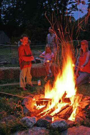People gather around the campfire at the New Canaan Nature Center. Photo: Contributed Photo