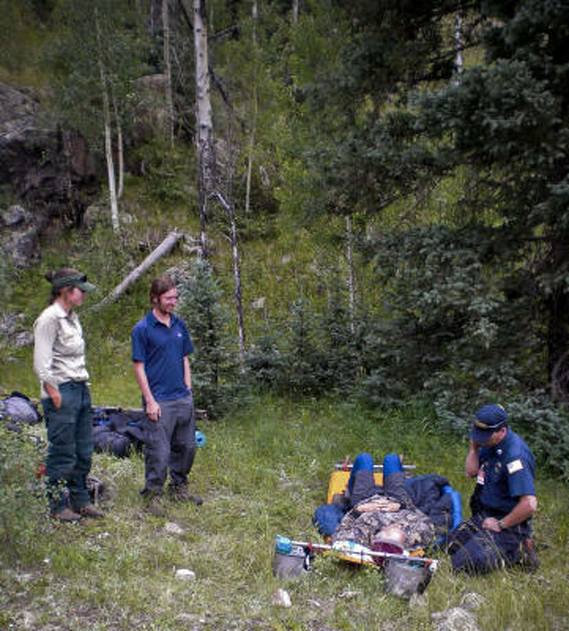 Don Leever is attended to by emergency personnel after being carried down the mountain by his troop of Boy Scouts while hiking in Colorado. Photo: Courtesy Photo