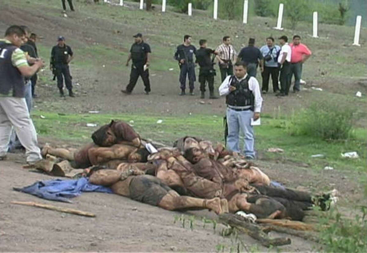 In this video frame grab, authorities gather at the crime scene in Michoacan state on Monday.