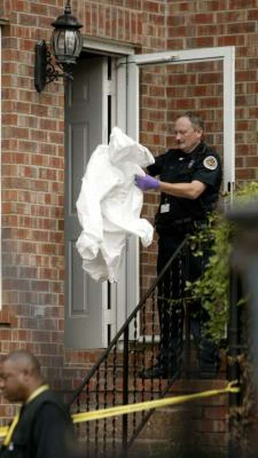 A police officer gets ready to process the Nashville apartment where Steve McNair was shot on Saturday. Photo: Ed Rode, AP