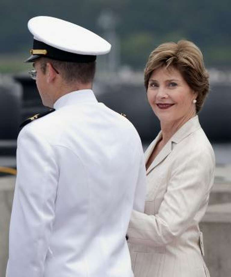 "Former first lady Laura Bush — accompanied by Lt. Cliff Jessop during a change-of-command ceremony for the USS Texas in Groton, Conn., on Friday — said she and her husband have been ""having a good time"" since leaving the White House. Photo: Thomas Cain, Associated Press"