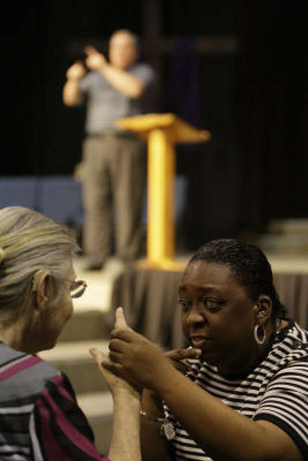 Jessie Hargrave, left, uses tactile signing to interpret the service at Woodhaven Baptist Deaf Church for Erica Griffin, who is blind and deaf. Photo: Melissa Phillip, Chronicle