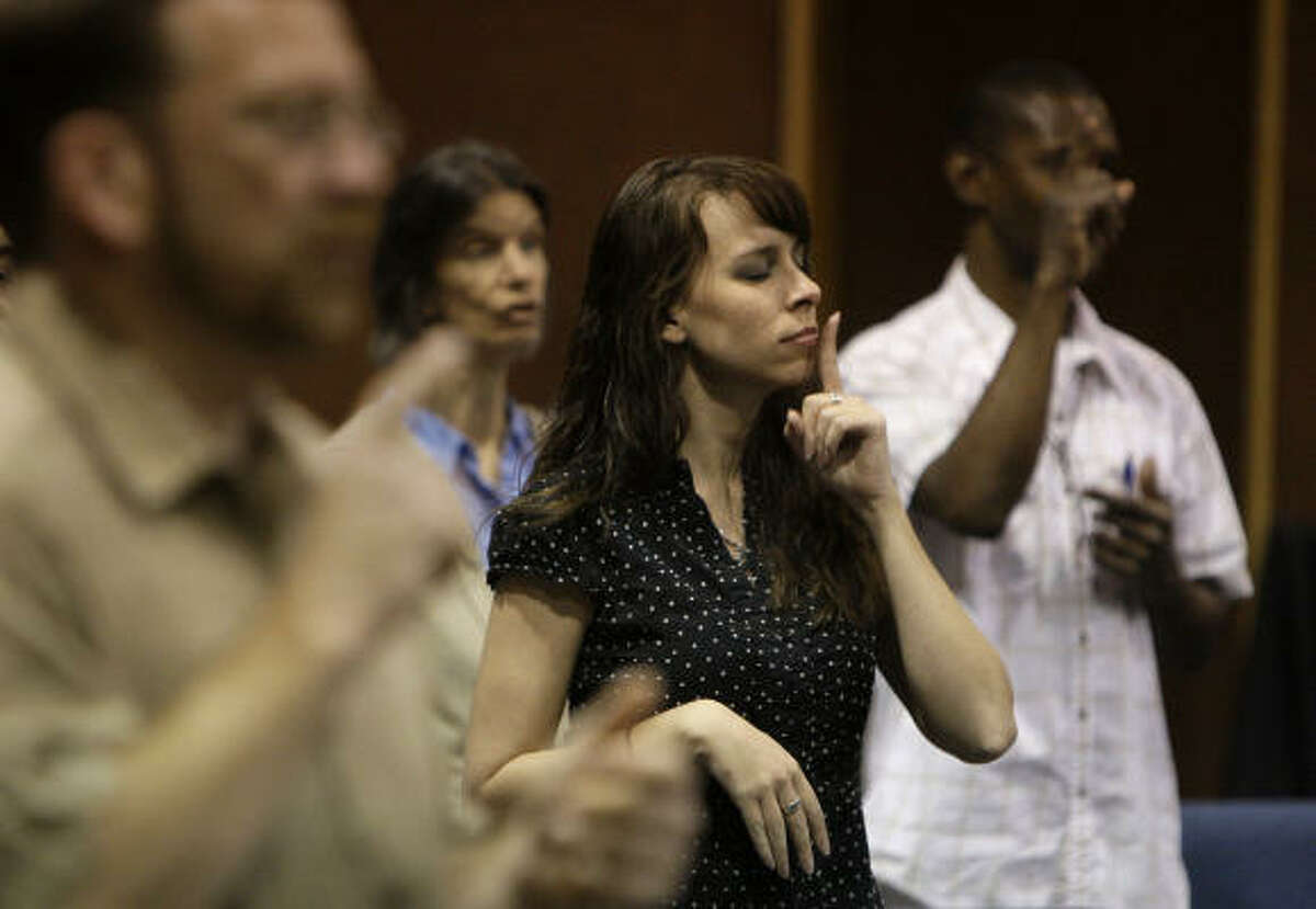 Piper Baumann and others at Woodhaven Baptist Deaf Church use sign language during a song at a recent Sunday service. The majority of the parishioners are deaf.