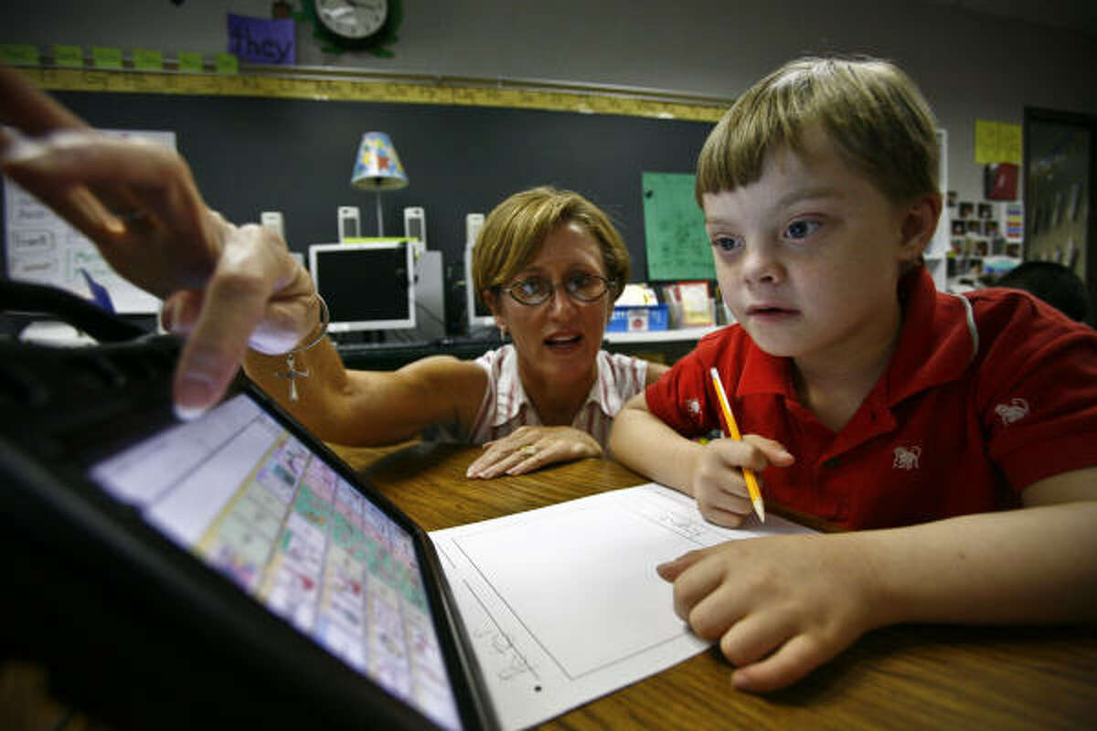 Aside from purchasing more technology, like the voice-output device used by Peter Bernay, 7, and Brookwood Elementary teacher Gwen Duhon, Clear Creek ISD will create 32 new positions, including eight elementary school teachers and two autism specialists.