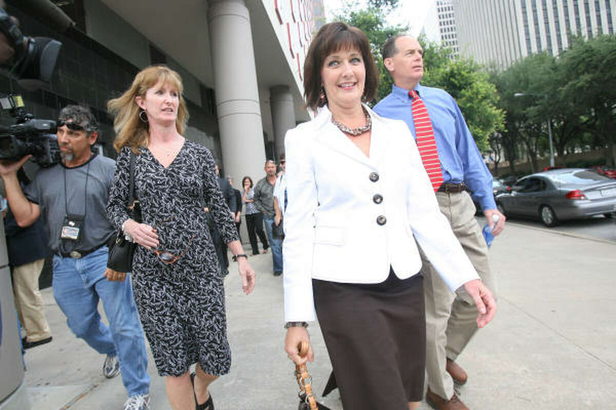Cathy McBroom, center, ex-case manager in Galveston, walks away from the Bob Casey Federal Court House on Monday.