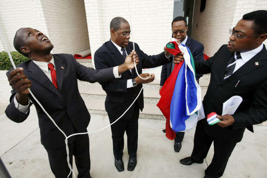 Officials prepare the flag of Equatorial Guinea to be raised at the nation's consulate in Houston. Photo: ERIC KAYNE :, FOR THE CHRONICLE