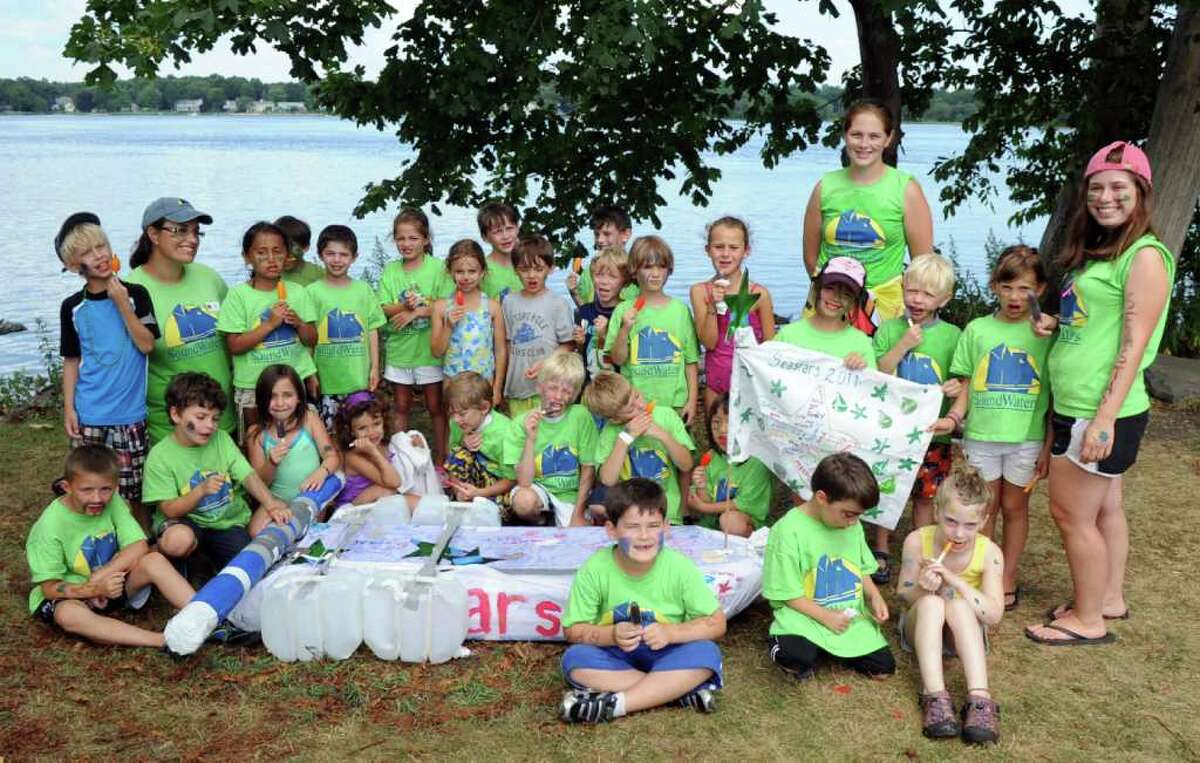 Members of the Seastars group pose for a photo around their winning boat on Thursday, August 4, 2011, after the Anything that Floats race at Cove Island Park in Stamford.