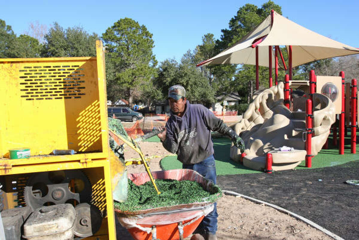 BE AN ANGEL: The barrier-free Be An Angel playground at Katy City Park, 5720 Franz Road, is nearing completion. Crews are working on the last phases of construction. Playground equipment has been installed. Final phases include installing playground surfacing and adding landscaping and tables. Pour-in-place cushioned flooring is being installed. Heluterio Fuga mixes up the mixture for the cushioned flooring.