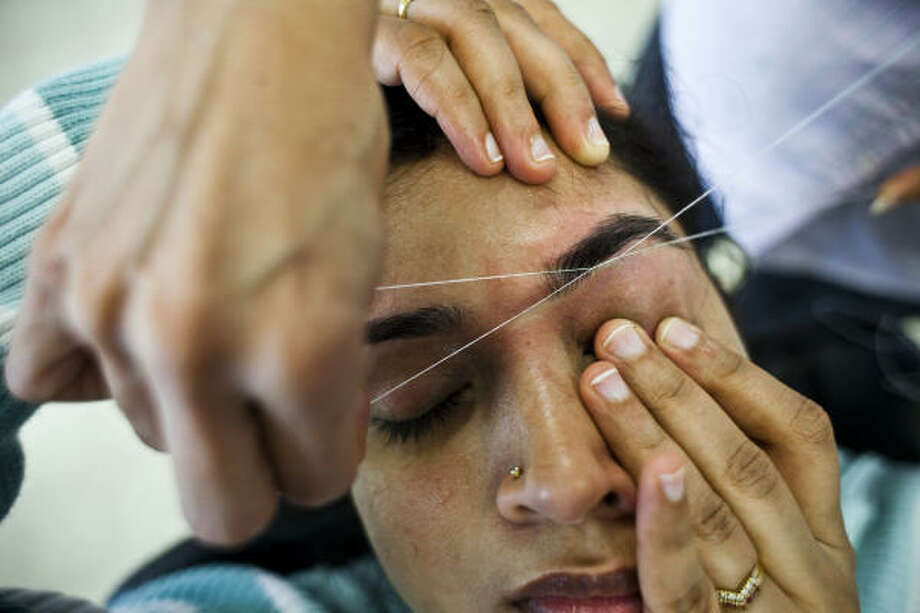 Mythili Muktevi performs cosmetic threading on a client at her salon in Pearland. She says licensing doesn't make sense because cosmetology schools don't teach threading. Photo: Eric Kayne, Chronicle