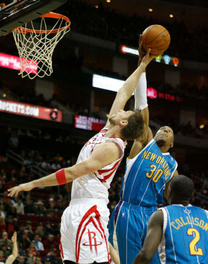 Hornets forward David West slaps the ball out of Rockets center David Andersen on a layup attempt in the second quarter. Photo: Julio Cortez, Chronicle