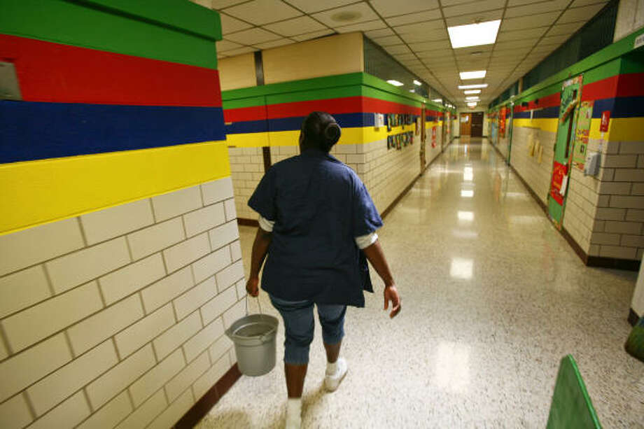 Carrie Miller walks through the empty hallways with a bucket of disinfectant at Mary McAshan Gibbs Pre-K Center on Tuesday in Huntsville after local schools shut down temporarily. Photo: Michael Paulsen, Chronicle
