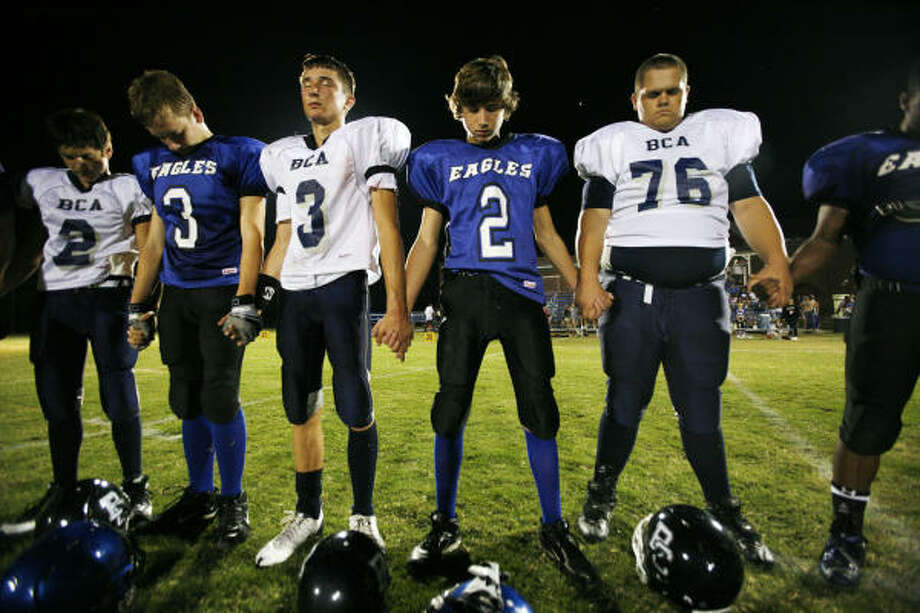 Players from both six-man football teams, Clear Lake Christian School Eagles and the Baytown Christian Academy Bulldogs, have a prayer following their game. Photo: Eric Kayne, For The Chronicle