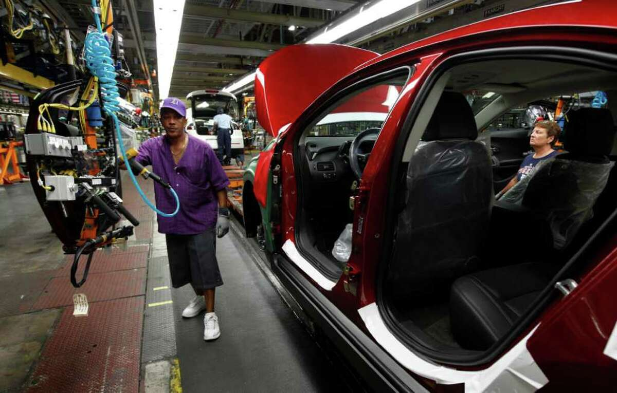In this July 27, 2011 photo, assembly line worker Edward Houie moves a door into position for a 2012 Chevrolet Volt at the General Motors Hamtramck Assembly plant in Hamtramck, Mich. General Motors Co. said Thursday, Aug. 4, 2011, its second-quarter profit nearly doubled to $2.5 billion as it got higher prices for its cars and trucks worldwide.(AP Photo/Paul Sancya)