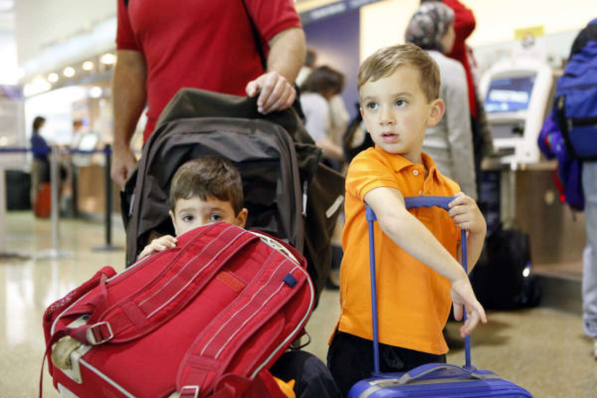 John Klosek and his sons Jack, 5, left, and Richie, 3, wait to go through security Tuesday at Hobby Airport.